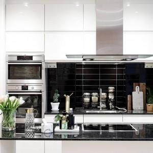 Powierzchnię nad blatem kuchennym wykończono - w kontrastującej elegancko z białymi meblami - czerni. Wykończone na połysk fronty szafek nadają kuchni ekskluzywny wyraz. Dwurzędowa zabudowa górna to również pojemny schowek na sprzęty kuchenne. Fot. Stadshem.se.