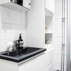 Płytka, ciemna umywalka efektownie kontrastuje z szafką, na której jest posadowiona oraz z białymi ścianami. Fot. Stadshem.se.
