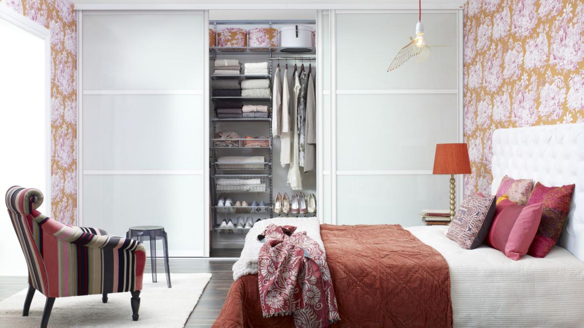 Doskonałym sposobem na zorganizowanie przestrzeni do przechowywania jest zabudowanie jednej ze ścian w sypialni. W takim rozwiązaniu pomogą drzwi przesuwne, które w swojej ofercie posiada firma Elfa. Dostępne są w trzech szerokościach, z wypełnieniem z forniru, melaminy, szkła, perspeksu lub pyty MDF i w  nieograniczonej palecie barw. Fot. Elfa.