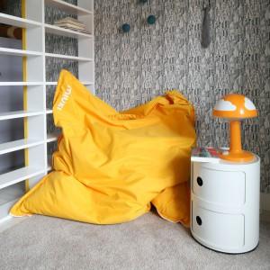Aby pokój nie wydawał się zbyt ponury, do aranżacji wprowadzono słoneczne akcenty. Wnętrze zdominowane szarością i błękitem ożywiają żółte detale: fotel w modnej formie worka oraz niewielka lampka z Ikei. Fot. Bartosz Jarosz.