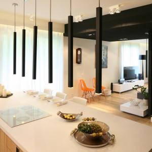 Czarne lampy w kształcie tuby zawieszone nad wyspą, oświetlają część roboczą, jak również wyznaczają granicę między kuchnią, a resztą domu. Projekt: Dominik Respondek. Fot. Bartosz Jarosz.