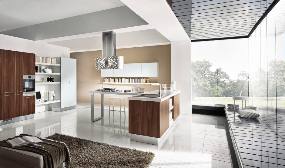 Nowoczesna kuchnia, w której monolityczną część wyspy wykończono w pięknym, czekoladowym wybarwieniu. Drewniany dekor ociepla nowoczesną formę mebli kuchennych i elegancko komponuje się w zestawie z bielą i elementami stalowymi. Fot. Home Cucine.