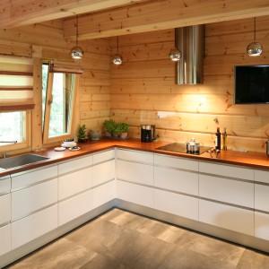 W tym ciepłym, urokliwym domu ścianę nad blatem pokrywa... drewniany bal. Kuchnia powstała bowiem w całkowitej harmonii z resztą wnętrza, gdzie również dominuje drewno. Naturalne bale pięknie wyglądają w zestawieniu z nowoczesną zabudową kuchenną. Aby nie ulegały szkodliwego wpływu wilgoci, chroni je przeźroczyste szkło. Projekt: Tomasz Motylewski i Marek Bernatowicz. Fot. Bartosz Jarosz.
