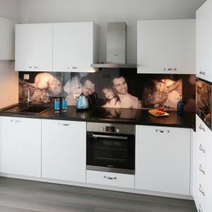 Aranżację prostej, białej kuchni urozmaica niebanalne rozwiązanie. Powierzchnię nad blatem kuchennym wieńczy kolaż rodzinnych zdjęć właściciela. Projekt: Joanna Nawrocka. Fot. Bartosz Jarosz.