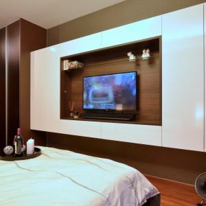 Telewizor w sypialni umieszczono w efektownej wnęce. Tłem dla sprzętu TV jest drewniana ściana, obudowana dużymi, gładkimi powierzchniami w wysokim połysku. Nad telewizorem zlokalizowano delikatną, szklaną półkę - jest praktycznie i estetycznie. Projekt: KNQ Associates. Fot. KNQ Associates.