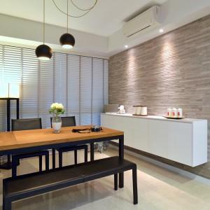 Rolę dekoracji w przestrzeni jadalni pełni efektowne, lekko loftowe oświetlenie oraz kamień na ścianie. Projekt: KNQ Associates. Fot. KNQ Associates.