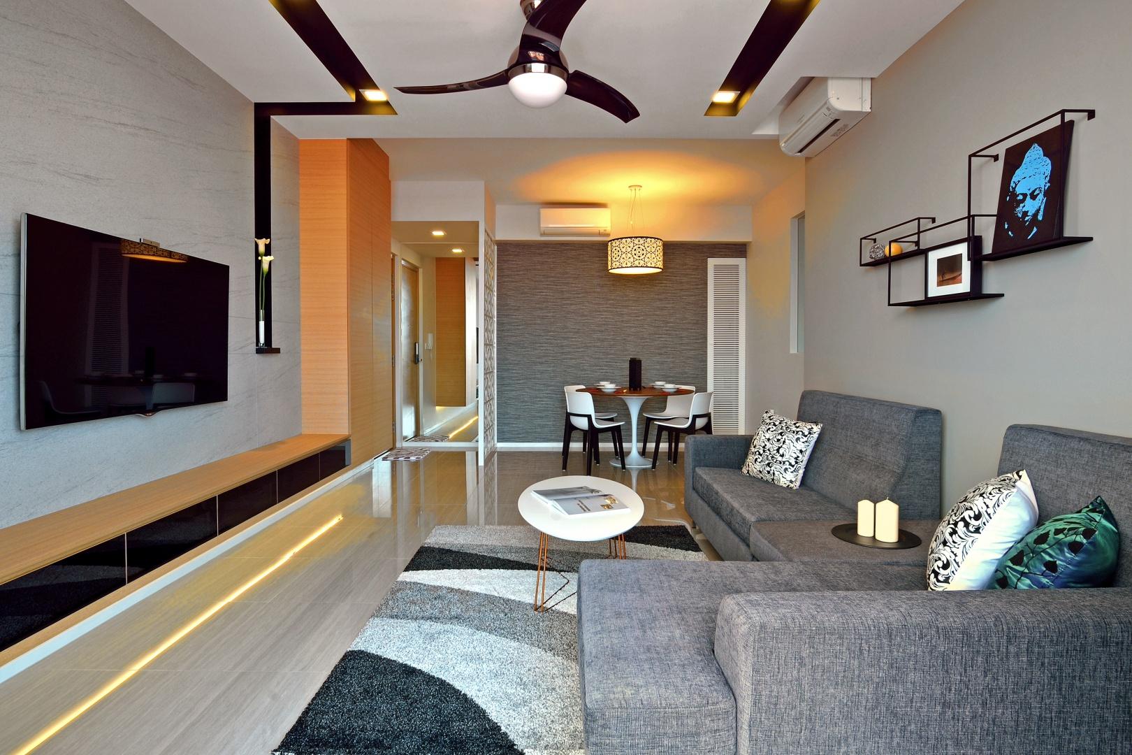 W salonie dominują stonowane barwy, a prym wiodą szarości. Szary jest komplet wypoczynkowy, ściana w jadalni, powierzchnia za TV, a nawet dywan. Wnętrze ożywiają ciepłe akcenty w kolorze drewna i czarne elementy. Projekt: KNQ Associates. Fot. KNQ Associates.