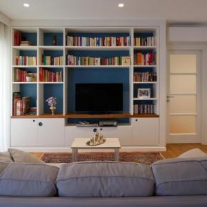 Alternatywna dla tradycyjnej meblościanki: wbudowanie jej w ścianę niezwykle urozmaica wnętrze. Półki są przestronne, a książki świetnie wyglądają na niebieskim tle. Ten kolor odnajdziemy także na oryginalnych kolistych uchwytach. Fot. Archifacturing.