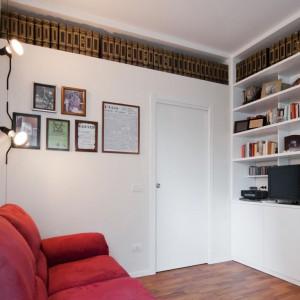 W tej aranżacji szczególną uwagę zwracają zwłaszcza długie półki pod sufitem, tym bardziej, że umieszczono na nich książki z jednej serii. Świetny sposób na oryginalne ozdobienie pomieszczenia. Fot. Archifacturing.