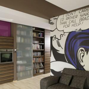 Pojemne półki na książki są częścią zabudowy pomiędzy kuchnią, salonem a przedpokojem, co jest rozwiązaniem oszczędzającym miejsce. Dodatkowo przesuwne drzwi zabezpieczają biblioteczkę przed kurzem i zapachami z kuchni. Projekt: Paweł Ejsmont. Fot. Bartosz Jarosz.