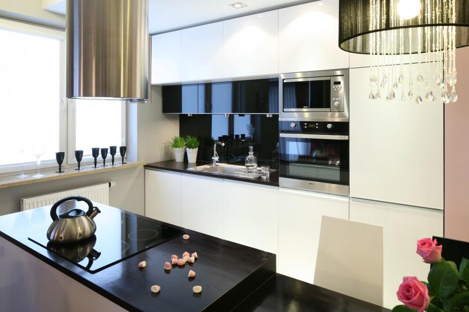 Czarna, połyskująca ściana nad blatem podkreśla glamourowy styl niewielkiej kuchni. Koresponduje też ze sprzętem AGD ukrytym w zabudowie. Projekt: Marta Dąbrowska. Fot. Bartosz Jarosz.
