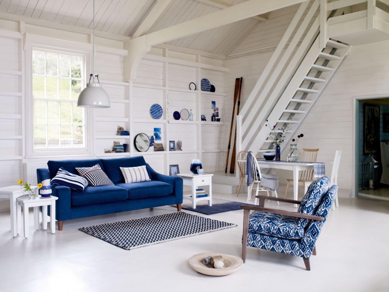 Salon urządzony w stylu skandynawskim urzeka prostotą oraz minimalistycznymi formami. Aby jasnemu wnętrzu nadać wyrazistego charakteru można przełamać je wypoczynkami w niebieskim kolorze. Fot. Marks&Spencer.