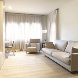 Salon urządzono w minimalistycznym stylu. Panuje tutaj elegancja i prostota, bez zbędnych dekoracji, które mogłyby przytłumiać przestrzeń. Fronty mebli pozbawione uchwytów, brak dywanu na podłodze oraz proste meble wypoczynkowe budują elegancki styl. Projekt: Coblonal Arquitectura. Fot. Coblonal Arquitectura.