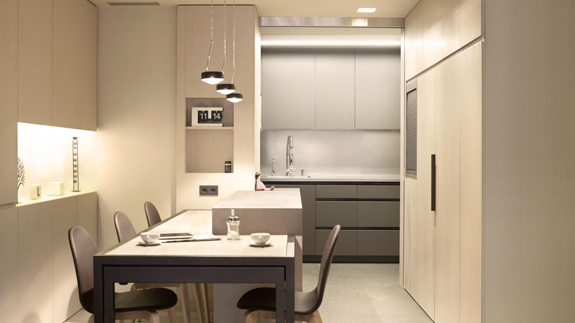 Jadalnia sąsiaduje z kuchnią, którą delikatnie przesłania, połączona ze stołem zabudowa, w której zaplanowano wnękę, pełniącą funkcję otwartych półek. Projekt: Coblonal Arquitectura. Fot. Coblonal Arquitectura.