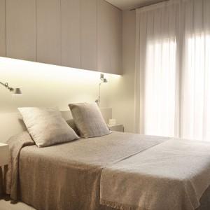 W sypialni małżeńskiej nad łóżkiem poprowadzono pas estetycznej zabudowy z z długimi szafkami, sięgającymi pod sam sufit. Dodatkowa powierzchnia do przechowywania, pozwala na estetyczne schowanie pościli, odzieży czy ręczników. Spód zabudowy dodatkowo podświetlono pasem LED-owym. Projekt: Coblonal Arquitectura. Fot. Coblonal Arquitectura.