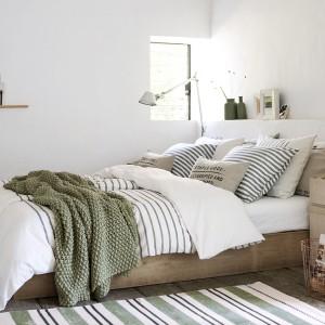 Zielona narzuta oraz wazony wprowadzają do wnętrza przyjemną atmosferę. Stonowana zieleń dobrze komponuje się z bielą ścian oraz naturalnym kolorem drewna. Fot. H&M home.