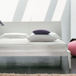 Biało-szarą sypialnię urozmaicono kolorowymi dodatkami. Różowa pufa, kolorowa poduszka i dekoracje umieszczone na półce ocieplają wnętrze. Fot. Bonaldo.