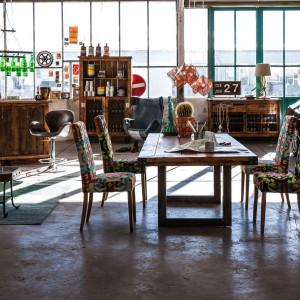 Skórzane kanapy, tapicerowane w tkaninie multikolorowe krzesła oraz stylizowane na stare drewniane meble to kwintensencja stylu vintage. Fot. Kare Design.