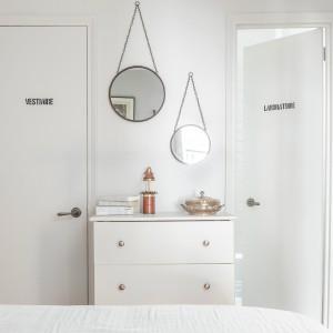 Z sypialni można bezpośrednio przejść do łazienki i wc, oryginalnie oznaczonych filuternymi napisami. Pomiędzy drzwiami ustawiono delikatną komodę z ozdobnymi metalowymi uchwytami, pełniącą rolę toaletki. Na ścianie zawisły dwa okrągłe lustra, pełniące jednocześnie funkcję dekoracyjną i czysto praktyczną. Projekt: Fanny Abes, The New Design Project. Fot. Alan Gastelum.