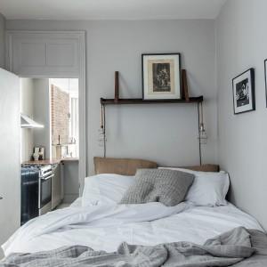 Za kuchnią ukryto... sypialnię. Oryginalne rozwiązanie aranżacyjne, pozwoliło do maksimum wykorzystać dostępną przestrzeń. W sypialni dominują delikatne, stonowane szarości, budujące przytulną atmosferę we wnętrzu. Oryginalnym elementem dekoracyjnym jest industrialne oświetlenie po obu stronach łóżka. Projekt: Fanny Abes, The New Design Project. Fot. Alan Gastelum.