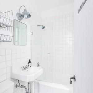 W niewielkiej, utylitarnej łazience króluje biel i funkcjonalne rozwiązania. Wszelkie dekoracje są oszczędne i utrzymane w industrialnej stylistyce. Metalowe półki, i vintage'owe lampy harmonizują ze skromnym lustrem. Projekt: Fanny Abes, The New Design Project. Fot. Alan Gastelum.