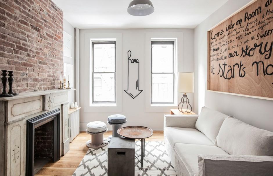 W niewielkim salonie, jasne kolory budują wrażenie przestrzenności a oryginalne dodatki podkreślają unikalność wnętrza. Na ścianie za kanapą zawisła duża drewniana rama, w którą oprawiono panel z ręcznie wykonanymi napisami. Usytuowany na przeciwległej ścianie kominek zaznaczono wyeksponowaną, surową cegłą. W centrum pomieszczenia znalazł się niebanalny stolik kawowy, z częścią monolityczną wykonaną betonu, oraz miedzianą tacą na metalowych nogach. Projekt: Fanny Abes, The New Design Project. Fot. Alan Gastelum.
