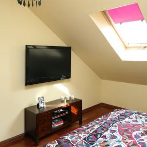 Naprzeciw łóżka znajduje się telewizor umieszczony na ścianie oraz mała szafka. Fot. Bartosz Jarosz.