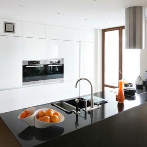Białą wysoką zabudowę kuchenną zestawiono z dużym, czarnym półwyspem. Białe meble zlicowano ze ścianą, a na ich tle efektownie prezentuje się ciemniejszy półwysep. Projekt: Izabella Korol. Fot. Bartosz Jarosz.