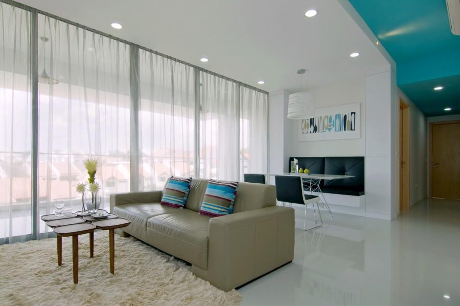 Panoramiczne przeszklenia, wyglądające na przestronny balkon są źródłem naturalnego światła, które wpadając do wnętrz, odbija się od białych ścian i dodatkowo rozświetla jasne wnętrze. Projekt: KNQ Associates. Fot. KNQ Associates.