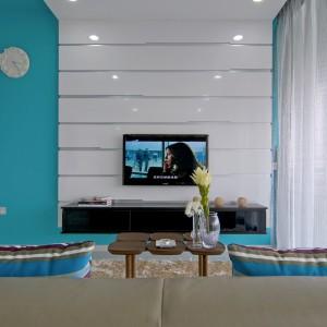 Telewizor w salonie umieszczono na białej zabudowie, wykończonej na połysk. Ta z kolei wyeksponowana została na tle soczystego turkusu. Projekt: KNQ Associates. Fot. KNQ Associates.