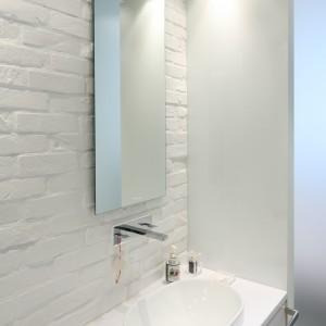 Surowa powierzchnia cegły malowanej białą farbą wprowadza do łazienki loftowy klimat, a  jednocześnie świetnie komponuje się z elegancką powierzchnią lakierowanych frontów meblowych. Fot. Bartosz Jarosz.