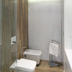 Oszczędność w stosowaniu kolorów i materiałów sprzyja spójności aranżacji. Zachowanie jednolitego wyglądu posadzki w całej łazience umożliwił również odpływ liniowy zainstalowany zamiast brodzika. Fot. Bartosz Jarosz.