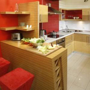 Meble kuchenne w kolorze ciepłego drewna znakomicie prezentują się na tle czerwonej ściany. Aranżację uzupełniają czerwone hokery oraz akcesoria kuchenne. Projekt: Inside Lab. Fot. Bartosz Jarosz.