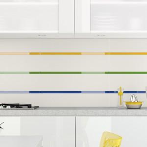 Ścianę w kuchni, w której dominuje biel wykończono białymi płytkami. Białą aranżację urozmaicają szklane inserty ułożone w formie kolorowych pasów, przecinających ścianę w trzech miejscach. Fot. Ceramika Opoczno.