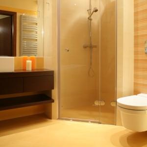 Łazienka dla rodzeństwa urządzona jest w słonecznym kolorze. Płytki w żółto-pomarańczowe pasy dodają energii i zapewniają pozytywny nastrój. Projekt: Kinga Śliwa. Fot. Bartosz Jarosz.