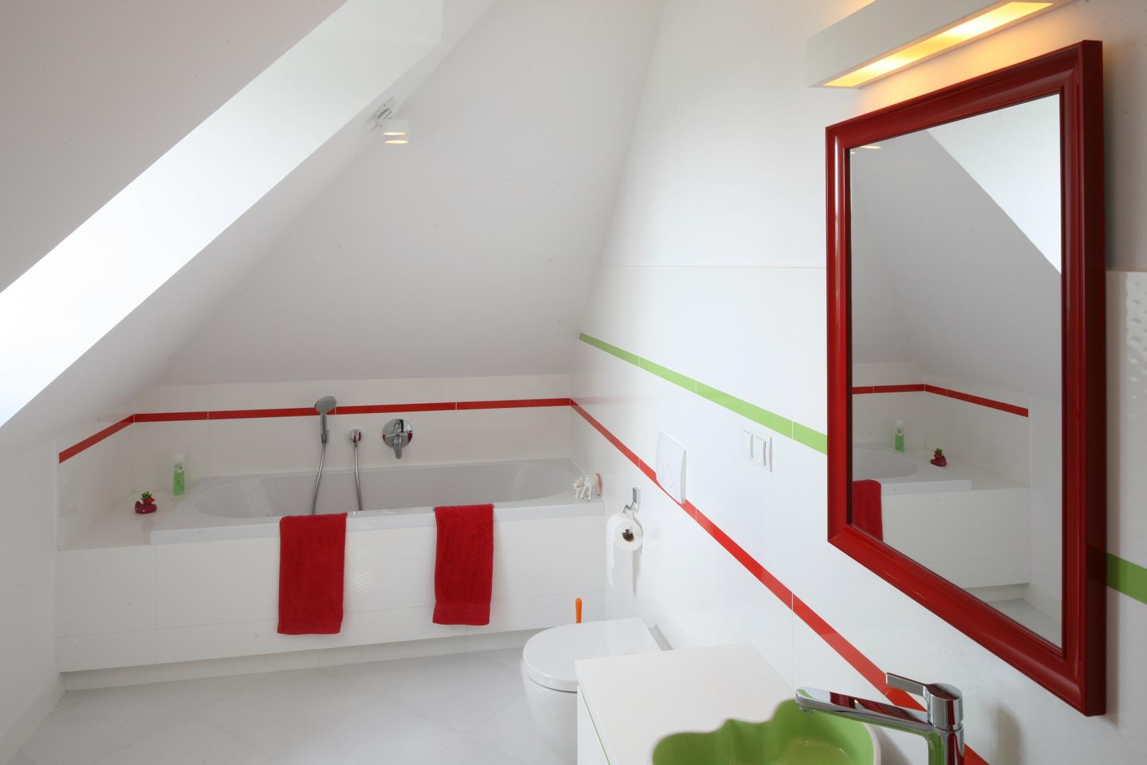Łazienka dla malucha ożywiona jest czerwienią i zielenią. Wokół wanny jest miejsce nie tylko na kosmetyki, ale także na zabawki, które towarzyszą dziecku w kąpieli.  Projekt: Katarzyna Merta-Korzniakow. Fot. Bartosz Jarosz.