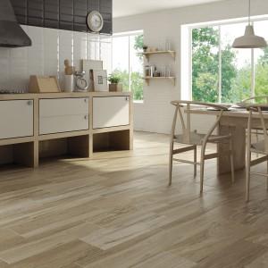 Piękne, drewnopodobne płytki ceramiczne w jasnym kolorze drewna idealnie wpisują się w przestrzeń tej jasnej kuchni z jadalnią. Fot. Halcon Ceramicas, kolekcja Amento.