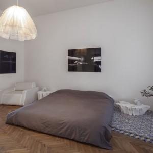 Choć mieszkanie zyskało nową, uwspółcześnioną organizację przestrzeni, zachowało się w nim wiele elementów typowych dla wnętrz w starych kamienicach. Niewielki salonik połączony jest z jednej strony ze strefą dzienną, z drugiej - z sypialnią, stanowiąc pokój przechodni. Projekt: destilat Design Studio. Fot. Monika Nguyen.