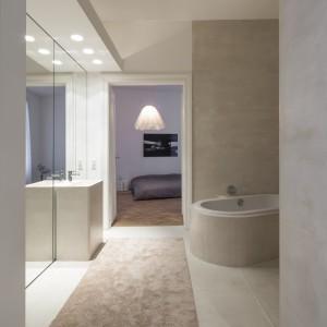 """Z korytarza do sypialni prowadzi \""""skrót\"""", poprowadzony przez łazienkę. Przejście to zaznaczono miękkim dywanikiem. Projekt: destilat Design Studio. Fot. Monika Nguyen."""