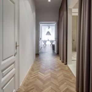 Podłogę w korytarzy i strefie dziennej wykończono parkietem, ułożonym w tradycyjną jodełkę. Projekt: destilat Design Studio. Fot. Monika Nguyen.