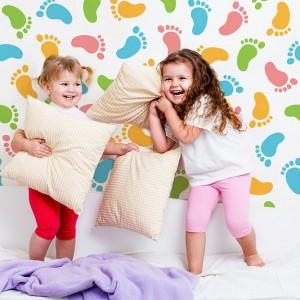 Tapeta Stópki, dostępna w sklepie Pixers, wygląda jakby ozdobiły ją maluchy przez odciśnięcie na papierze stóp umoczonych w kolorowej farbie. Fot. Pixers.