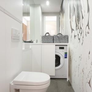 Chociaż łazienka ma szerokość jedynie 1,2 m zmieściła się tutaj nawet pralka ukryta w zabudowie pod blatem.  Projekt: Karolina Łuczyńska. Fot. Bartosz Jarosz.