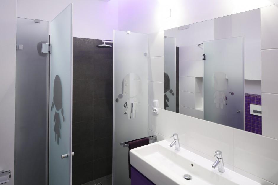 Dobrym patentem na wąską łazienkę jest wnęka prysznicowa w głębi pomieszczenia. Tę zamknięto taflami mlecznego szkła z uroczym wzorem, który informuje, że to łazienka dla dziewczynek. Projekt: Michał Mikołajczak. Fot. Bartosz Jarosz.