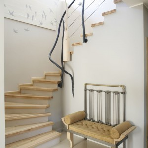 Dekoracyjna balustrada nawiązuje do motywów przyrody, która była inspiracją aranżacji domu. Na uwagę zasługują też malowane ręcznie jaskółki, zdobiące ścianę przy schodach. Projekt: Marta Kruk. Fot. Bartosz Jarosz.