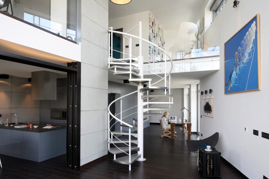 Kute, metalowe schody pomalowane na biało wyglądają niezwykle lekko i dekoracyjnie. Są ciekawym elementem dekoracyjnym strefy dziennej na dolnej kondygnacji dwupoziomowego loftu. Projekt: Justyna Smolec. Fot. Bartosz Jarosz.