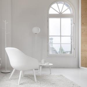 Meble dopasowano kolorystyką do barw, w jakich wykończono wnętrze. Białe krzesło, lampy i stolik kawowy scalają się wizualnie w stanowiących dla nich tło, białej podłodze i ścianach. Projekt: i29 interior architects. Fot. Ewout Huibers.