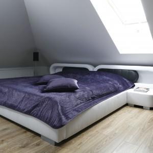 Główne miejsce w tej nowoczesnej sypialnia na poddaszu zajmuje duże, wygodne łóżko. Ciekawie prezentuje się szczególnie jego zagłówek. Projekt: Marta Kilan. Fot. Bartosz Jarosz.