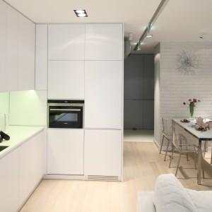 Biała minimalistyczna kuchnia, połączona z jadalnią i salonem zyskała szorstki detal, kontrastujący fakturą z gładkimi powierzchniami w postaci białej cegły. Projekt: Monika i Adam Bronikowscy. Fot. Bartosz Jarosz.