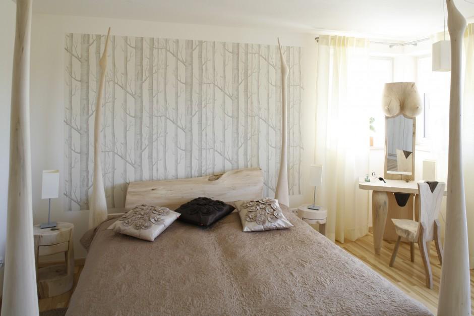 W tej sypialni drewno zastosowano trochę mniej tradycyjnie, dzięki czemu jest ona nie tylko niezwykle przytulna, ale również bardzo oryginalna. Uwagę przyciąga wykonane na zamówienie u artysty łóżko oraz ciekawa toaletka czy szafki nocne. W tak zaplanowaną aranżację świetnie wpisuje się także delikatna fototapeta z motywem drzew. Projekt: Marta Kruk. Fot. Bartosz Jarosz.