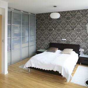 Najmocniejszym elementem sypialni jest ściana za łóżkiem. Jej dynamiczny wzór doskonale uspokajają proste formy mebli oraz oświetlenia. Drewniana podłoga w ciepłym, jasnym wybarwieniu dodaje wnętrzu przytulności. Doskonale pasuje również do dekoracyjnej ściany. Projekt: Michał Mikołajczak. Fot. Monika Filipiuk-Obałek.